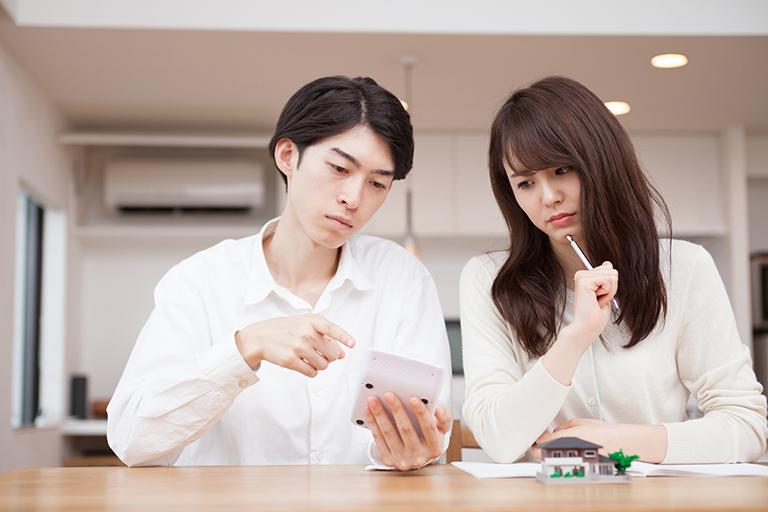 写真:建設費用を計算する夫婦